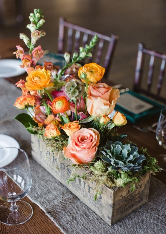 An advantage of wooden containers over glass for your centerpiece? You can plant flowers directly into them for a slightly longer bloom life not to mention natural feel!