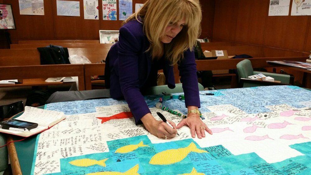 Laura Turner Seydel, Chairperson of the Captain Planet Foundation signs Hannah's traveling quilt ( #quiltagainstplastic ) on Plastic Pollution Awareness Day in Atlanta.