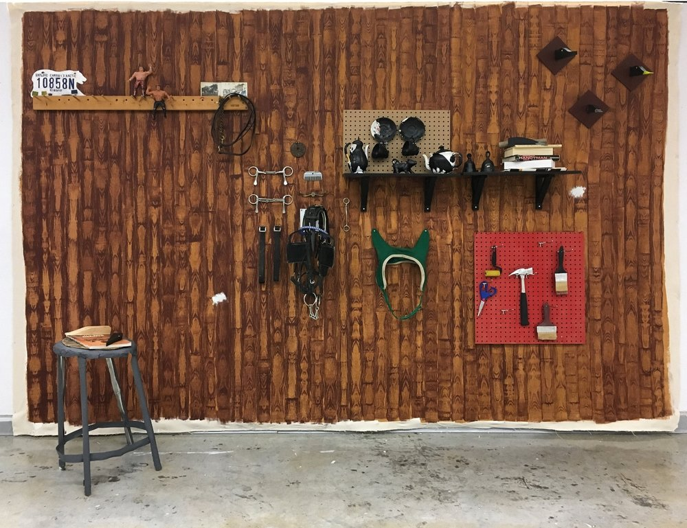 Man-Cave 2,  2017. Acrylic on canvas, wood, aluminum, wrestling figurines, horse tack, vintage tea set, found books and magazines, shelving, coat rack, hardware. Painted backdrop measures approximately 8' x 15'