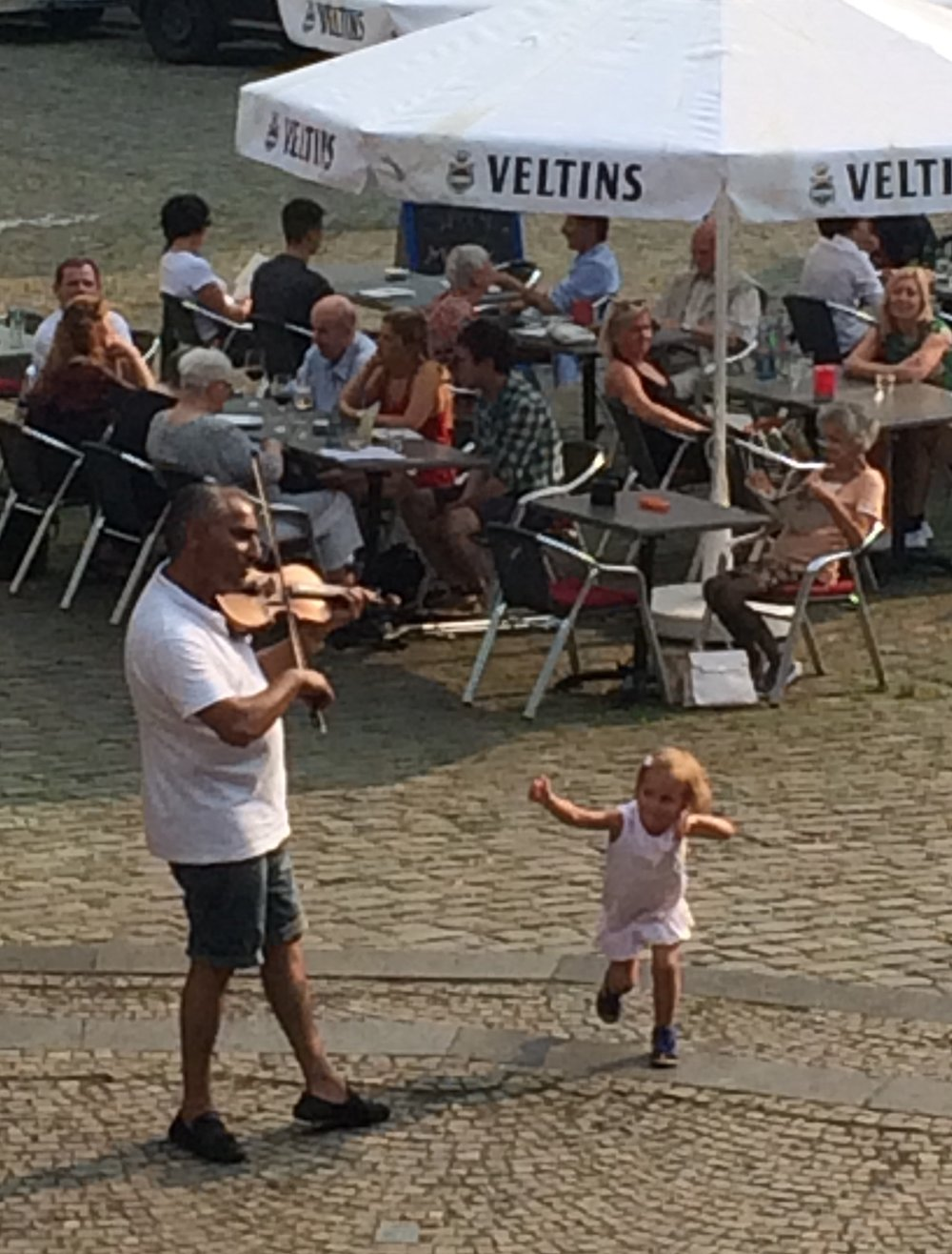Man playing the violin in Solingen, a child leaps up and dances
