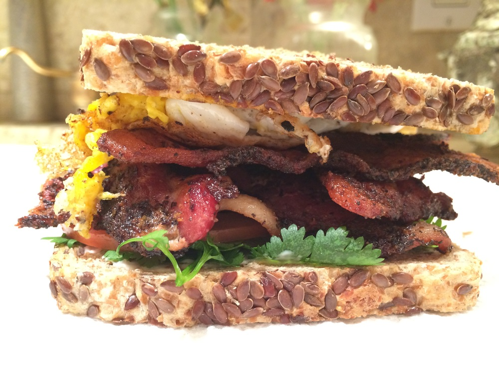 "B.L.T. 2"" X 4"" X 4""   Fresh local tomatoes, cilantro, local free range egg, pepper bacon, revival market mustard on   Ezekiel flax seed bread toasted"