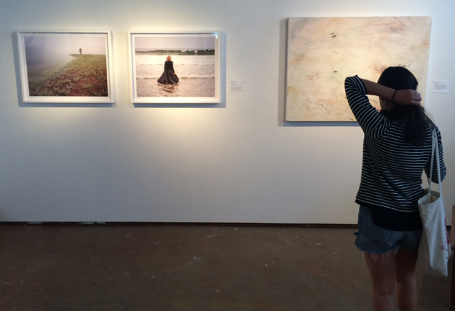 Gallery visitor takes in photographs by Marna Clarke and a painting by Toni Littlejohn.