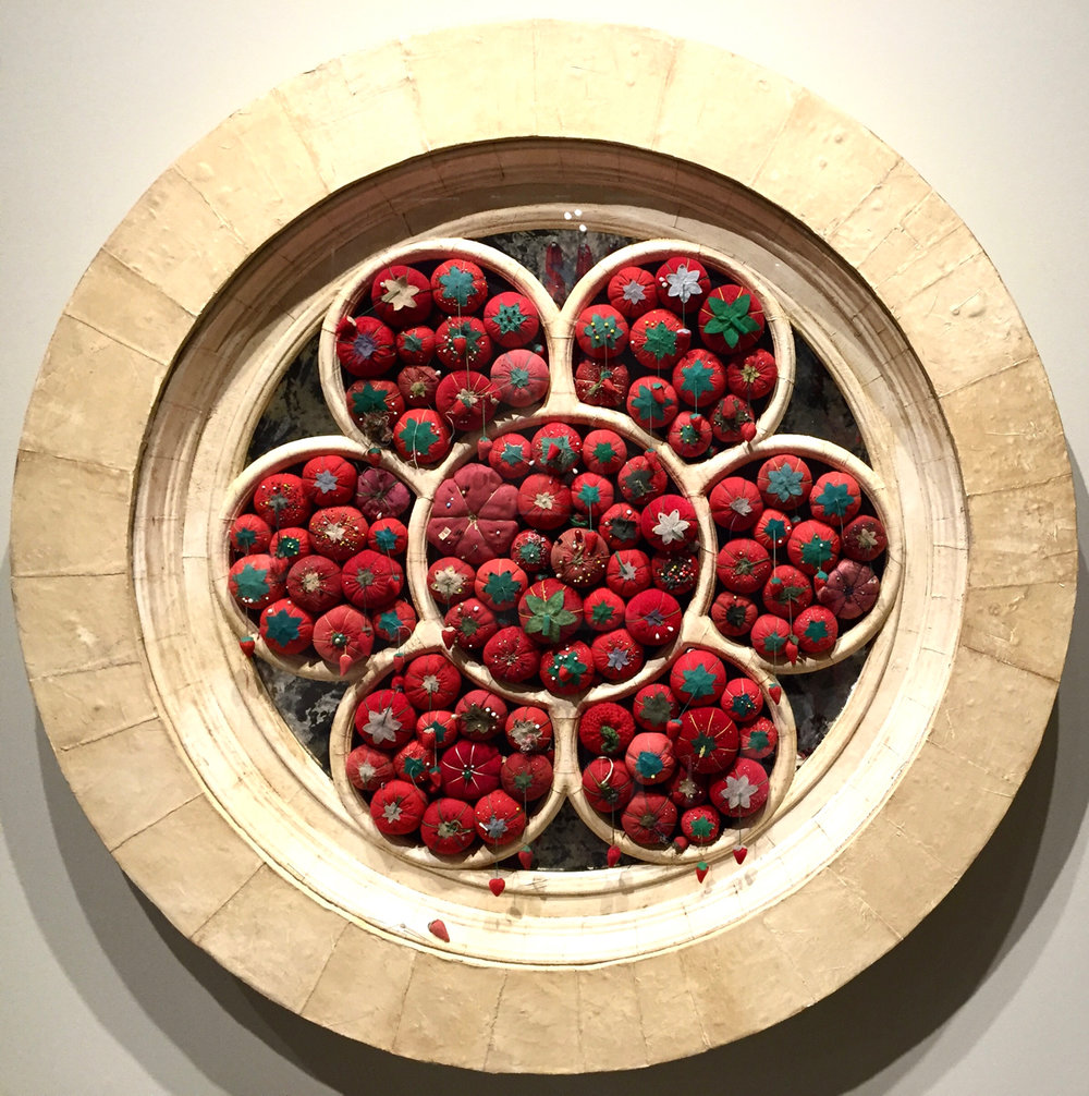 "This piece, made of tomato shaped pincushions, wood, plaster, and mirrors is called "" Rose Window ,"" and it is part of  Marianne Lettieri's exhibit, ""Reflections.""  It is on display at the  Museum of Craft and Design  in San Francisco through January 22, 2017."