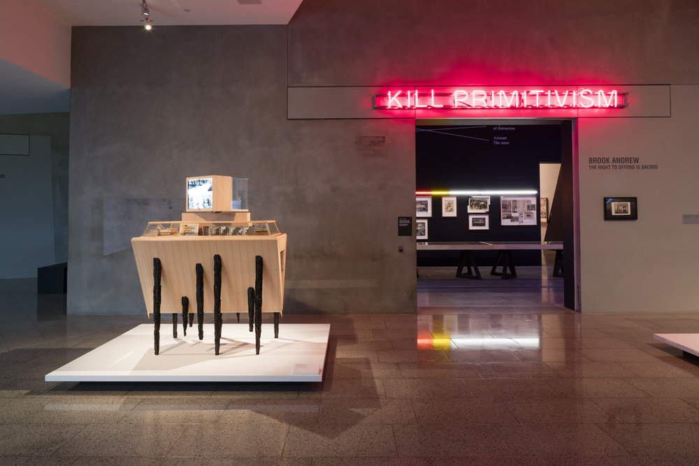 The Right to Offend is Sacred  National Gallery of Victoria, Melbourne March 3 – June 4, 2017 Installation view. Photo: Dianna Snape.  In re-discovering and re-positioning a complex practice, Brook Andrew: The Right to Offend is Sacred includes many of Andrew's most memorable works, contextualised in exciting new ways, juxtaposed with formative works that have had very limited exposure. As a map that scopes, records and pinpoints great moments in Andrew's career, this solo exhibition will also include a new sculptural work, enabling viewers to intuit future directions in the artist's ever changing practice. These sculptures, like much of Andrew's work, will draw on the artist's extensive personal archive and respond to important themes in his practice that issue from and resonate in books, objects, photographs and postcards, newspapers and the media. The exhibition also confirms the importance of the collaborative process in Andrew's practice.