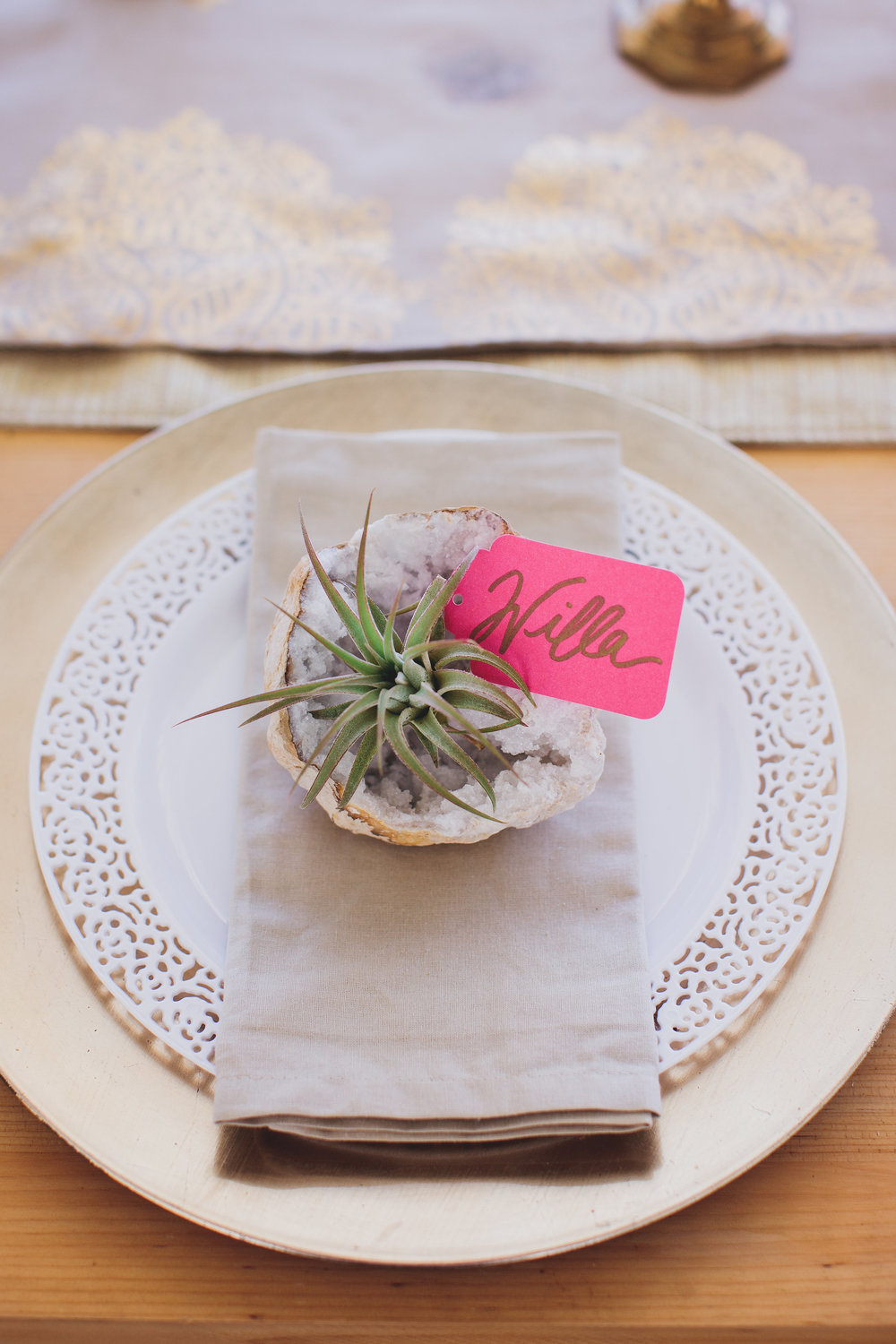 A geode and airplant place setting with oatmeal linens and gold chargers.
