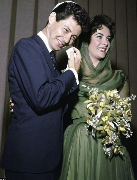 Elizabeth Taylor dressed in sophisticated sage with yellow-white-sage bouquet