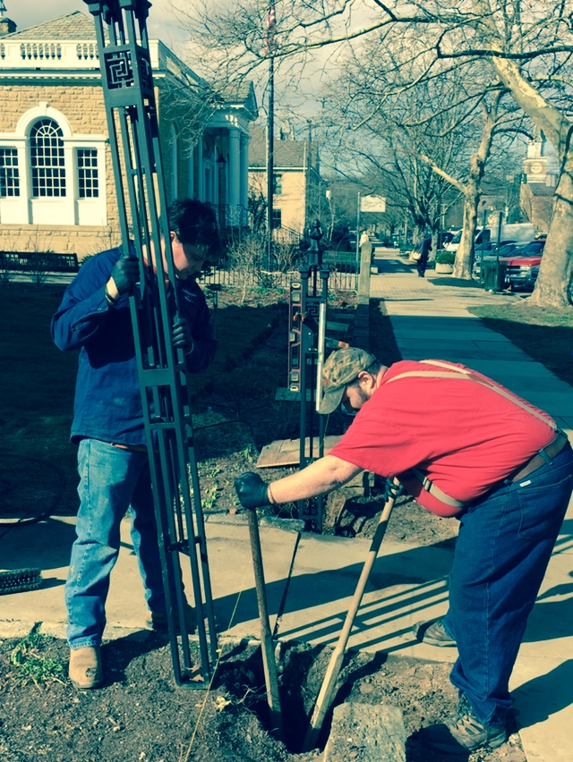 James Sayre and Brendan Kennedy, employees of Eagle Machine and Welding, set the gate post for the new fence.