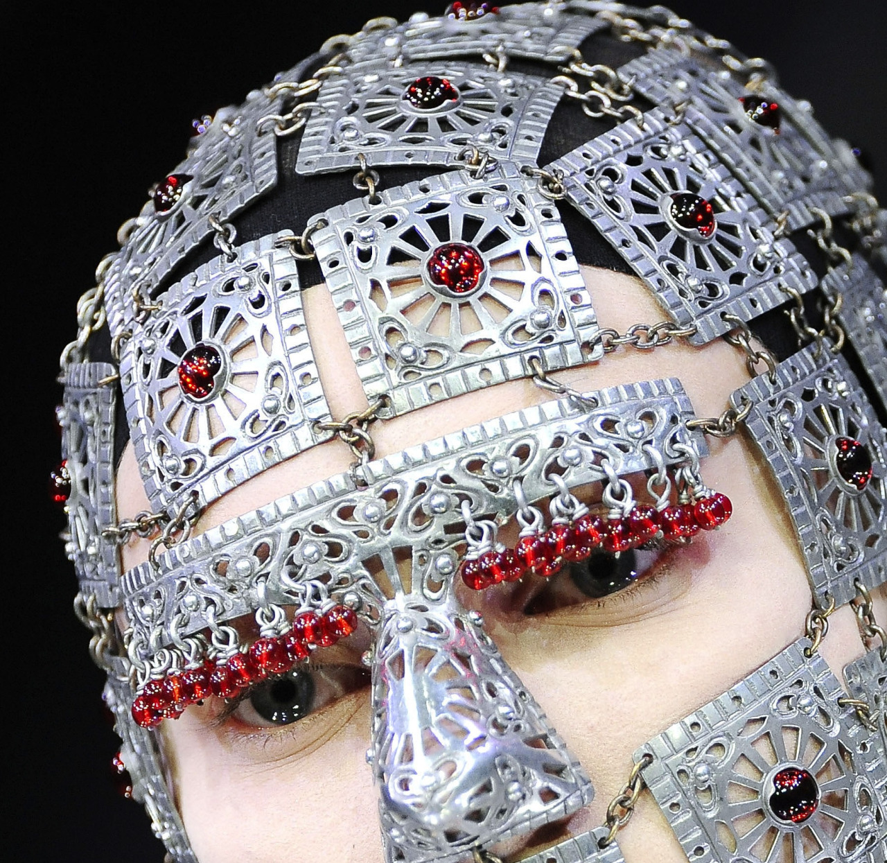 Model wears metal filigree head armourwith red gems dripping over her eyes at Alexander McQueen F/W 2009 'Horn of Plenty'