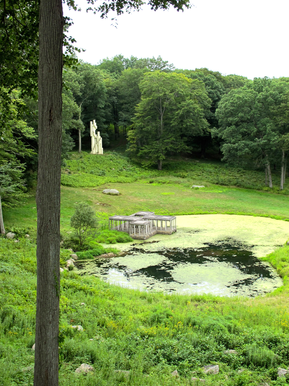 Pavilion in the Pond  (foreground) plays with scale to make it seem much further away than it is. In the background,  Monument to Lincoln Kirstein , 1985, that Johnson had built in honor of his friend and poet, Lincoln Kirstein.