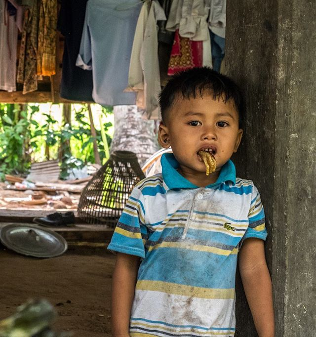 A boy chews on a left over chicken foot in a village close to Siem Reap, Cambodia. #cambodia #travel #siemreap #portrait