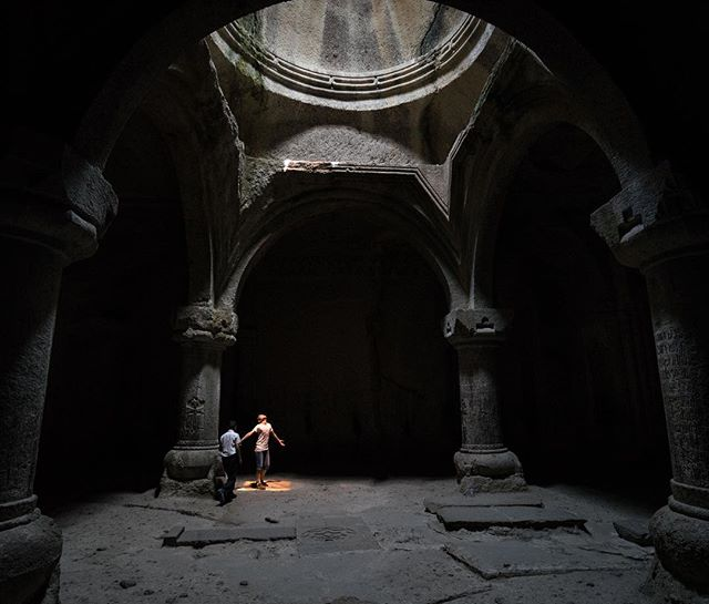 A boy stands in the orange light coming through a stained glass of the minarete at Geghard monastery, Armenia. The chapel complex is carved out of the rock-face, an almost unbelievable feat given it was built over 800 years ago.