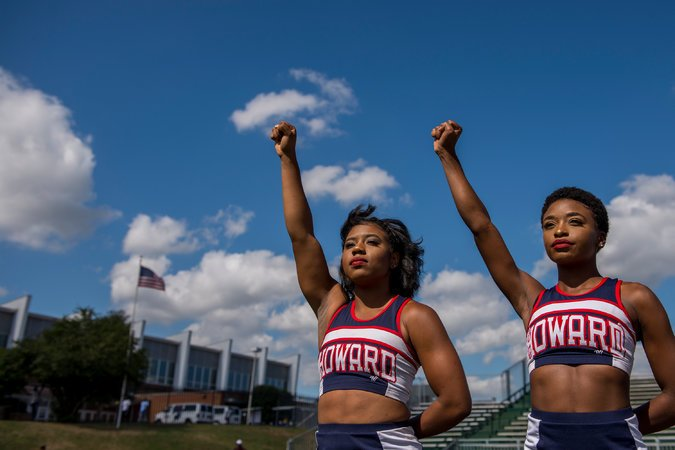 "Howard university cheerleaders raise their fists in protest during the playing of ""lift every voice and sing."""