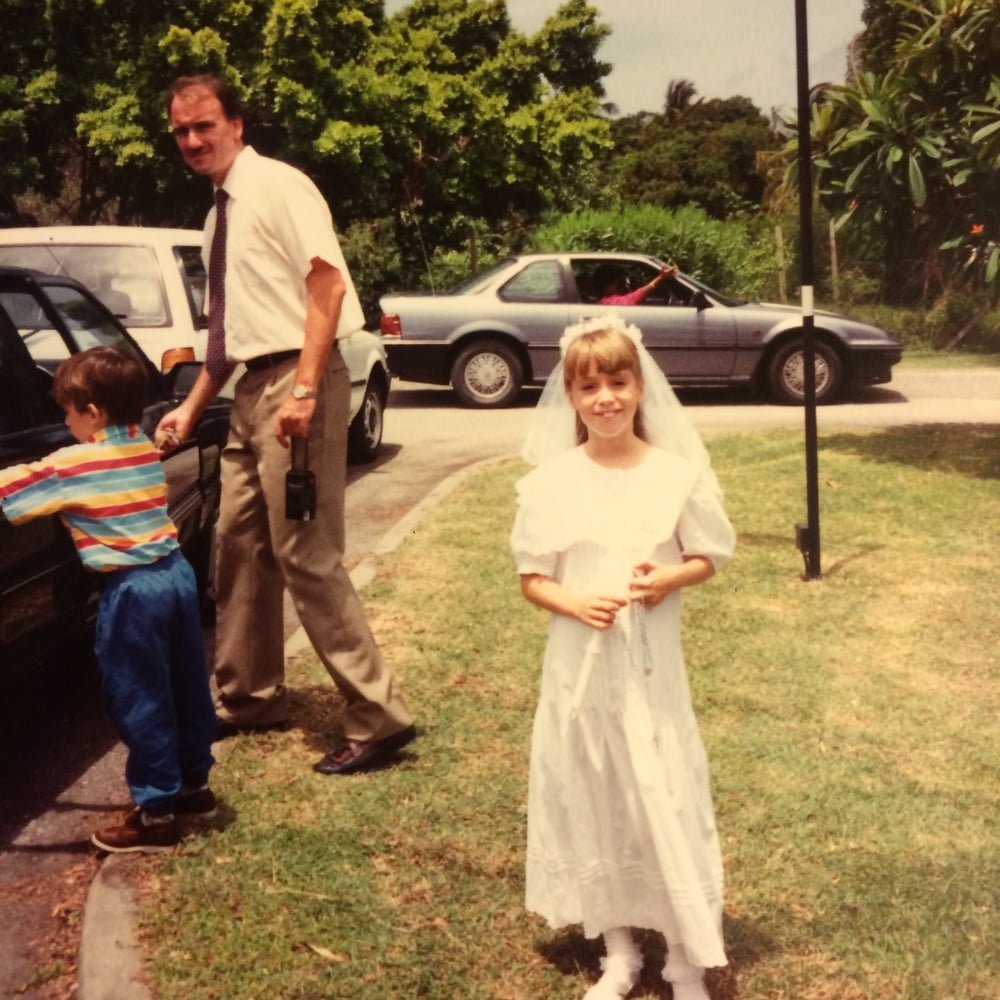 Me, en route to church for my first communion, hence the mini-bride garb.  Daddy is to the left, loading my brother into the car and looking generally thrilled to be there.