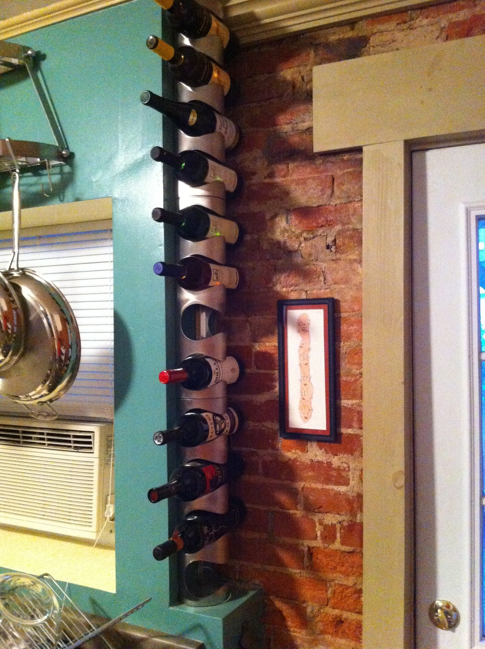 Eric uses all the vertical space in the kitchen with a wall mounted pots and pans holder, knife magnet, and stacked wine rack.