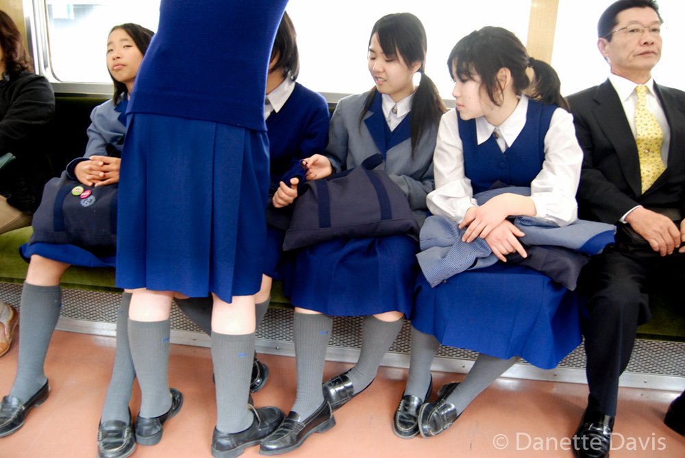 School Girls on a Train - Tokyo,  Japan    I'm always amused by this picture because of the expression of the two passengers who noticed me photographing. The intent was to photograph the uniform shoes.