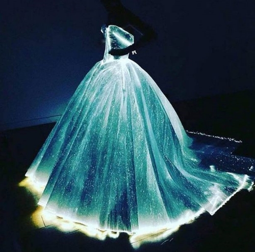 "The ""Luminate"" dress: fiber optic woven organza from France, with 30 mini battery packs sewn into the gown's understructure. The gown is hollow underneath (no tulle!) – holding its own structure."