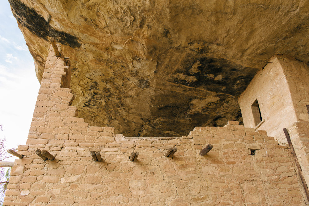 """This wall is incredible - it used to go from """"floor"""" to """"ceiling."""" It was built to protect the food from invaders - a lot of Indian massacres were taking place in this era, and Balcony House likely stored food for a few different dwellings, not just this one. Protecting the food from invaders was crucial to survival."""