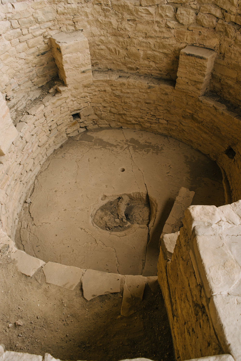 """This Kiva is actually built incorrectly, but this perspective shows you some of the details. The """"shelf"""" looking thing in the bottom is a deflector. There's a hole to let in fresh air, and the deflector prevents that air from hitting the fire pit and blowing the smoke all over the Kiva. The ledge at the bottom of this picture is supposed to be with the hole for air. They constructed it incorrectly and had to re-make it."""
