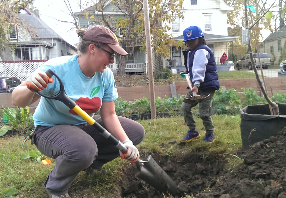 Amanda working on a planting project with a neighborhood kiddo