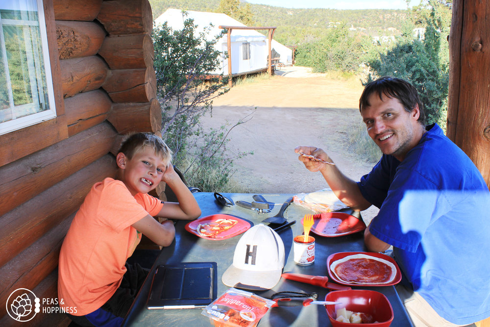 "Back in ""civilization"" at our cabin near Zion, eating tortilla pizzas cooked over the fire. They are as tired as they look!"