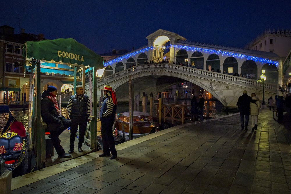 VENICE, ITALY - DECEMBER 08:  Three gondoliers chat near a Christmas decorated Rialto Bridge on December 8, 2011 in Venice, Italy.