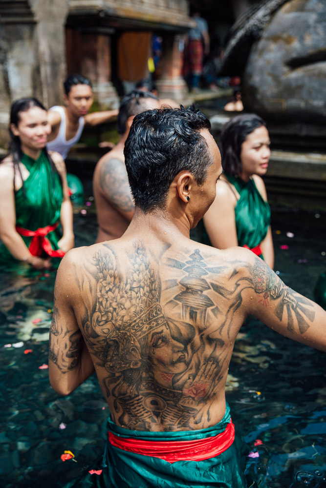 A man with an intricate tattoo bathes in the springs.