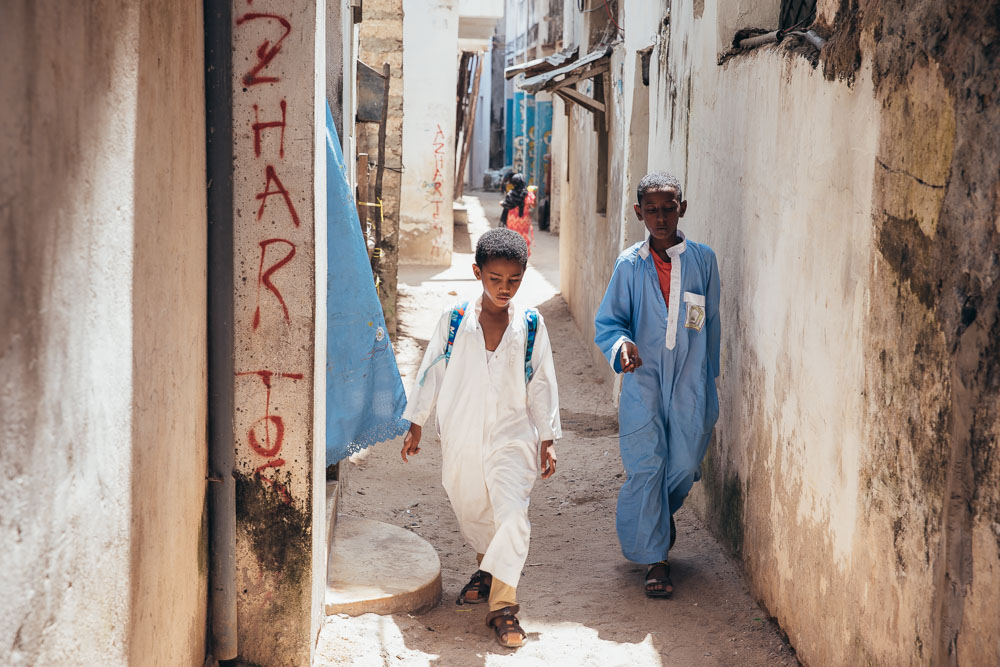 Young boys walk through the alley.
