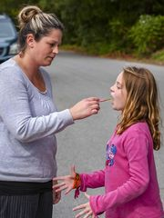 Megan Vaughan administers a dose of hemp oil to her 10-year-old daughter Aurora Husk outside the Bristol Elementary School on Friday, October 2, 2015. Husk, who has intractable epilepsy, is not allowed to consume the oil on school property. Her mother comes to the school twice a day to give her two of her three daily doses. (Photo: GLENN RUSSELL/FREE PRESS)