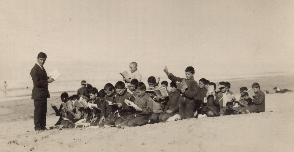 A group of boys from Antilyas Orphanage attend lessons on the beach c. 1925