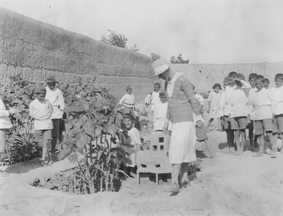 A relief worker inspects a mud house built by young boys in the garden at Alexandropol.