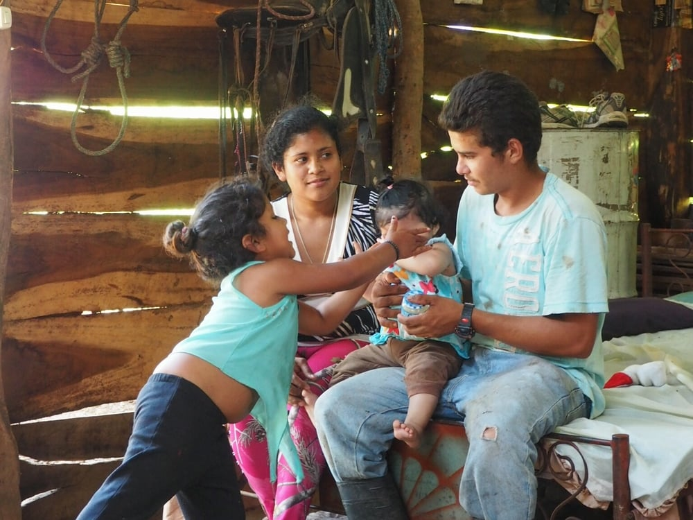 "This is Alejandro (23) with his wife Maria (19), their infant daughter and Alejandro's niece. They live in a section of   Isiquí called El Carizo, which is only reachable via a steep, 30min hike from the center of the village. They have no running water, no latrines and the only electricity available is provided by a solar panel. They would have loved to host two Venturers, but our project partner deemed El Carizo unsafe, claiming that ""the people of El Carizo go out to drink and party on the weekends""."