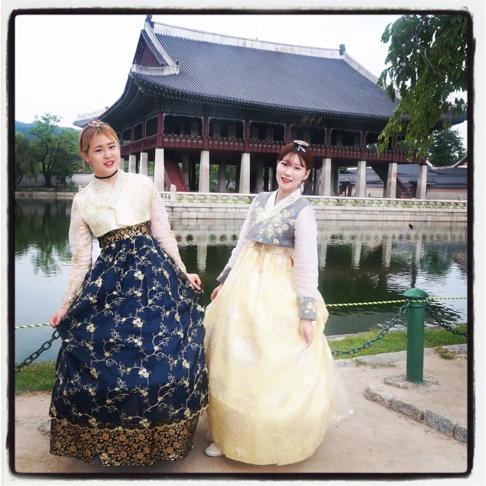 "Two Korean visitors to the Gyeongbok Palace ""perform"" Korean Tradition in the ultimate arena of Authenticity, the ""souvenir shop"" of national tourist sites."
