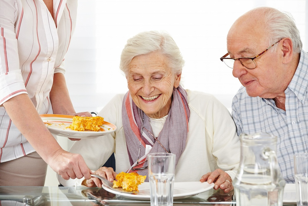 Senior citizens couple eating lunch at nursing home