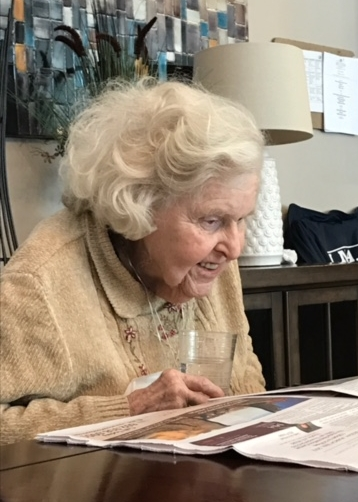 One of our residents enjoying an article published in the Pebble Creek Post, written about her and her dog.