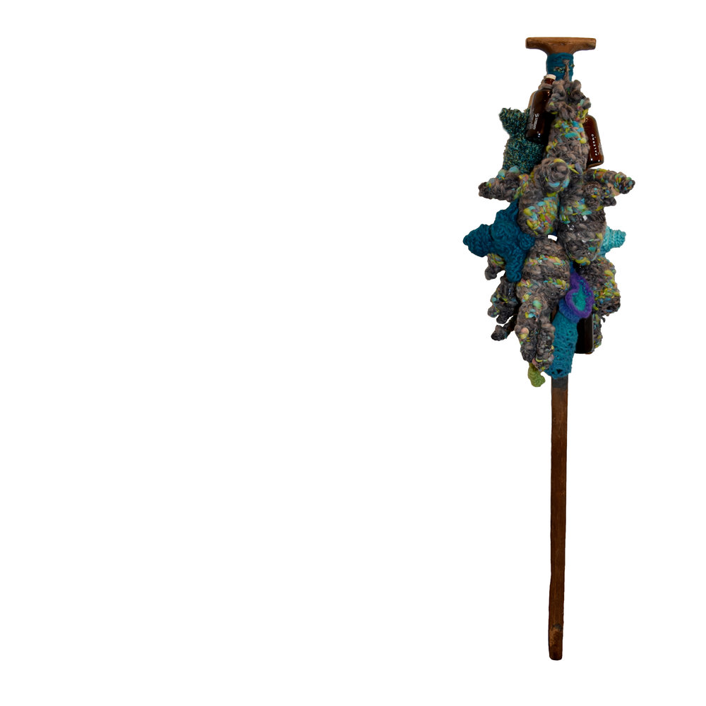 shaman staff  53 x 18 x 12 inches, vintage scythe, bottles filled with infused oils, yarn, up-cycled grocery bags (stuffing).  Symbolic of the Axis Mundi, a space navigated by shaman as a transitional point between the conscious and unconscious or celestial pole between worlds. Traditionally feminine, the omphalos (umbilicus), is the center of the world.   An vintage agricultural tool has lost it's blade and is recontextualized as the base for a shaman stick. Found bottles are filled with herbal infusions and with yarn, converted to a grouping of dangling fertility sculptures/talisman.