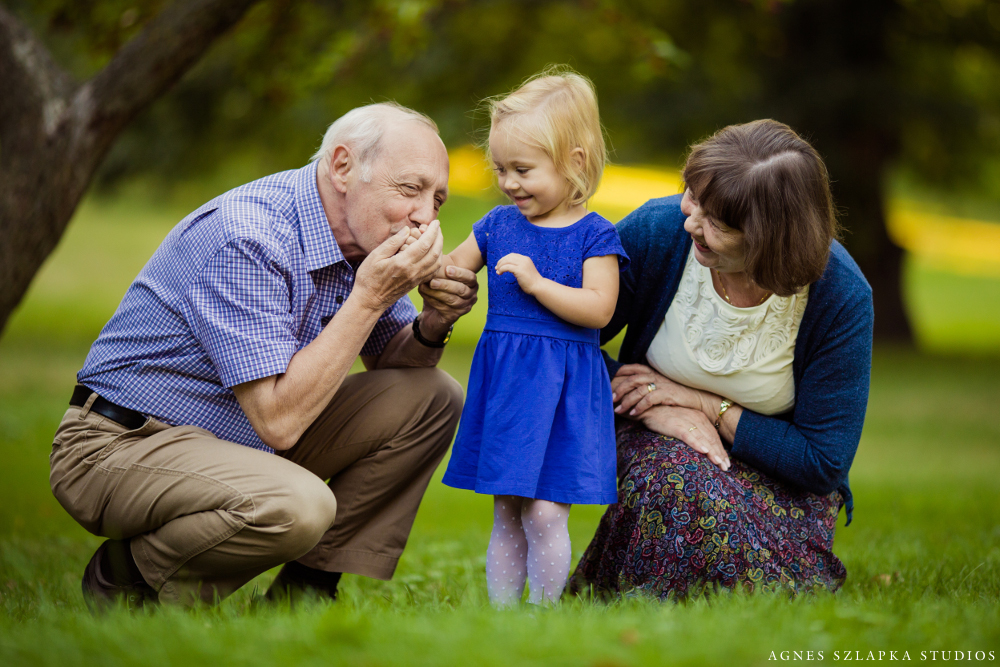 grandpa kissing granddaughters hand in park | cleveland ohio family photographer