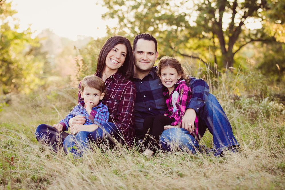 family of four sitting on grass smiling - cleveland photographer