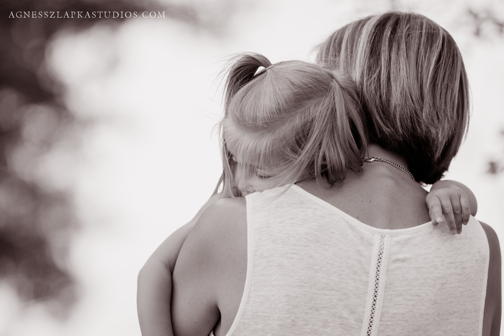 mom embracing toddler daughter smiling | cleveland, OH lifestyle motherhood photographer