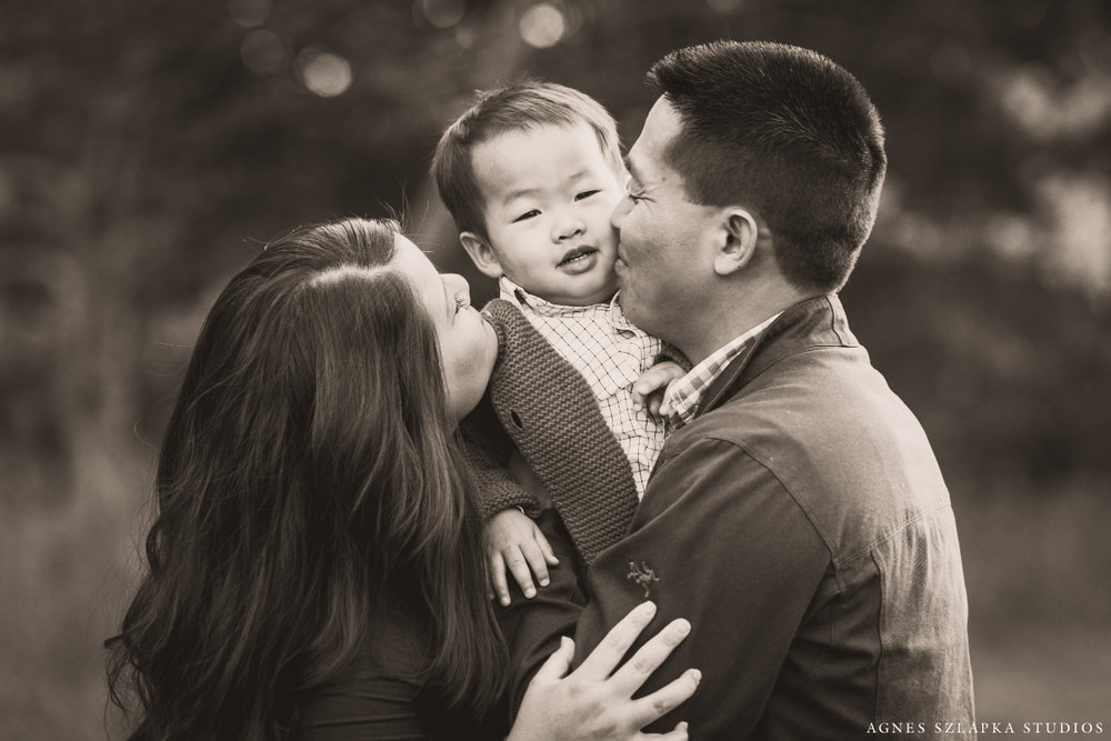 parents kissing baby boy cheeks | cleveland family photographer