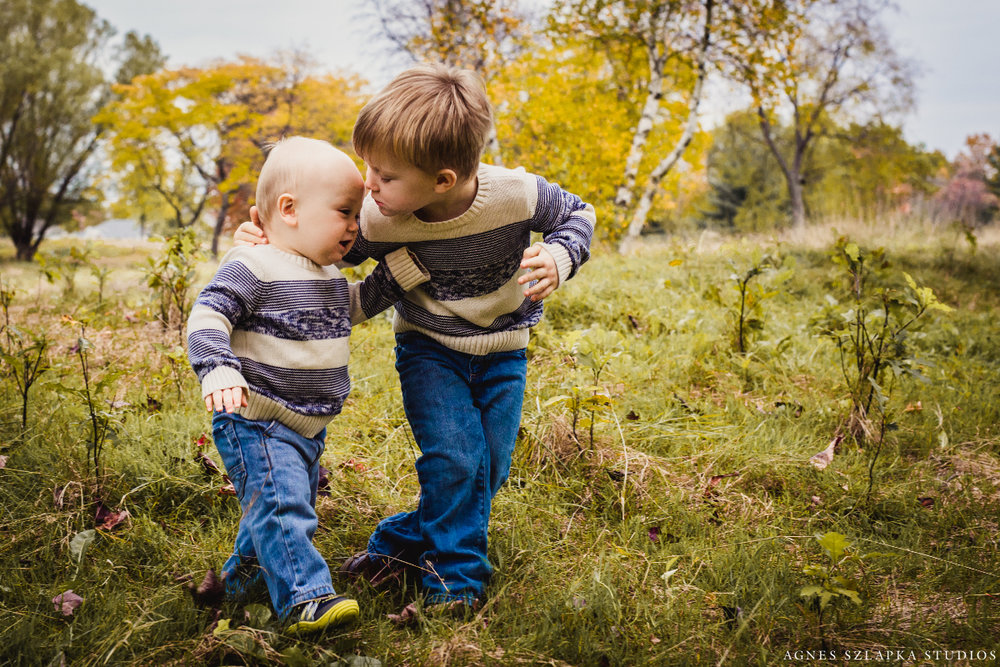 two bothers walking and whispering in ear | cleveland ohio lifestyle family photographer