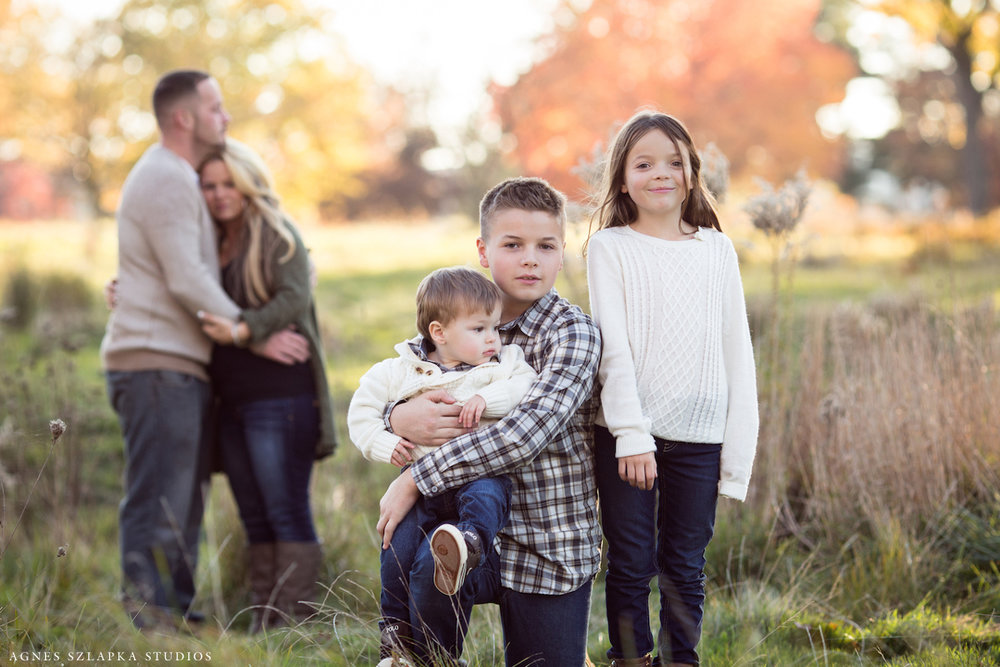 three siblings with parents looking on | cleveland, ohio lifestyle portraits