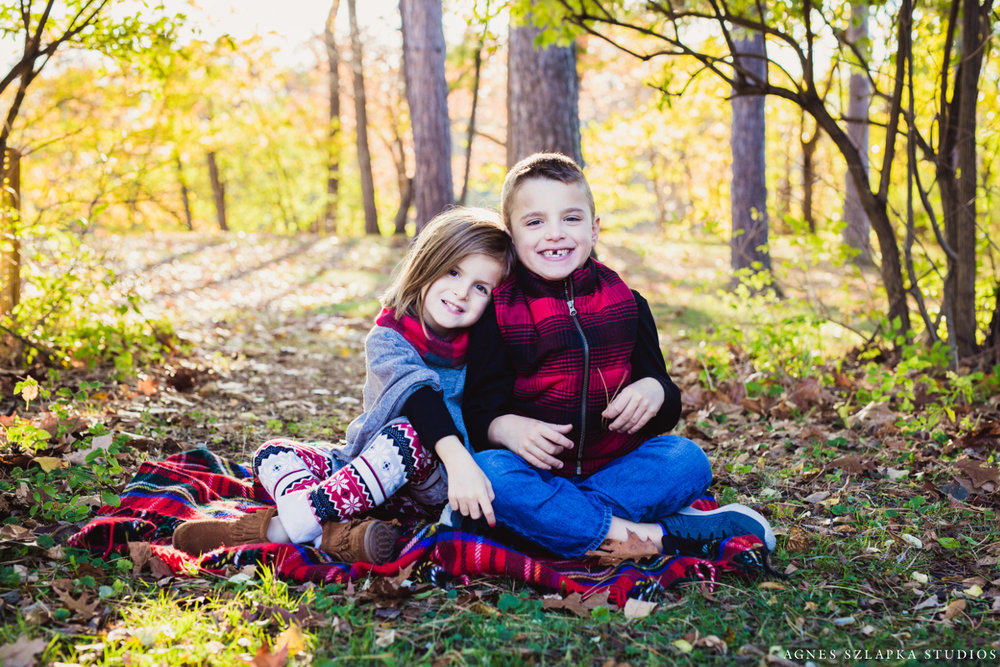 brother and sister sitting on grass smiling wearing plaid | cleveland, Ohio family photographer