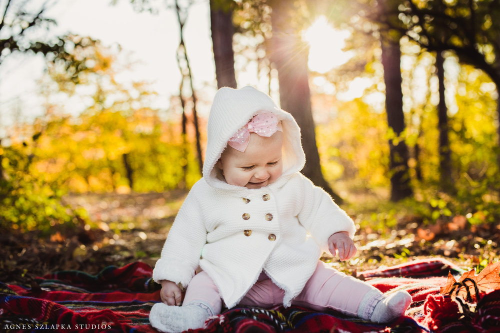 sweet baby girl playing with hands in park during fall | cleveland, ohio family photography