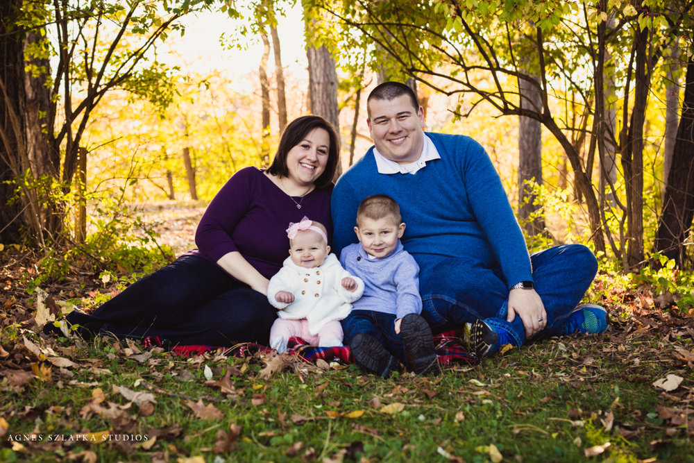 parents and two small kids sitting on the ground in park | cleveland, ohio family photography