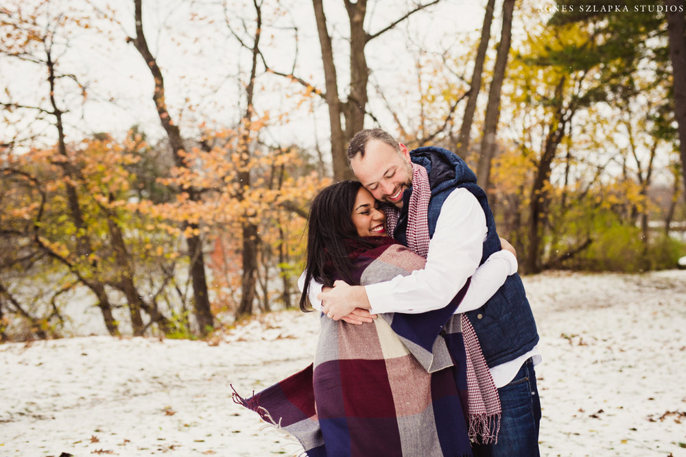 mom and dad squeezing tight to stay warm on snowy day | cleveland, ohio family portraits