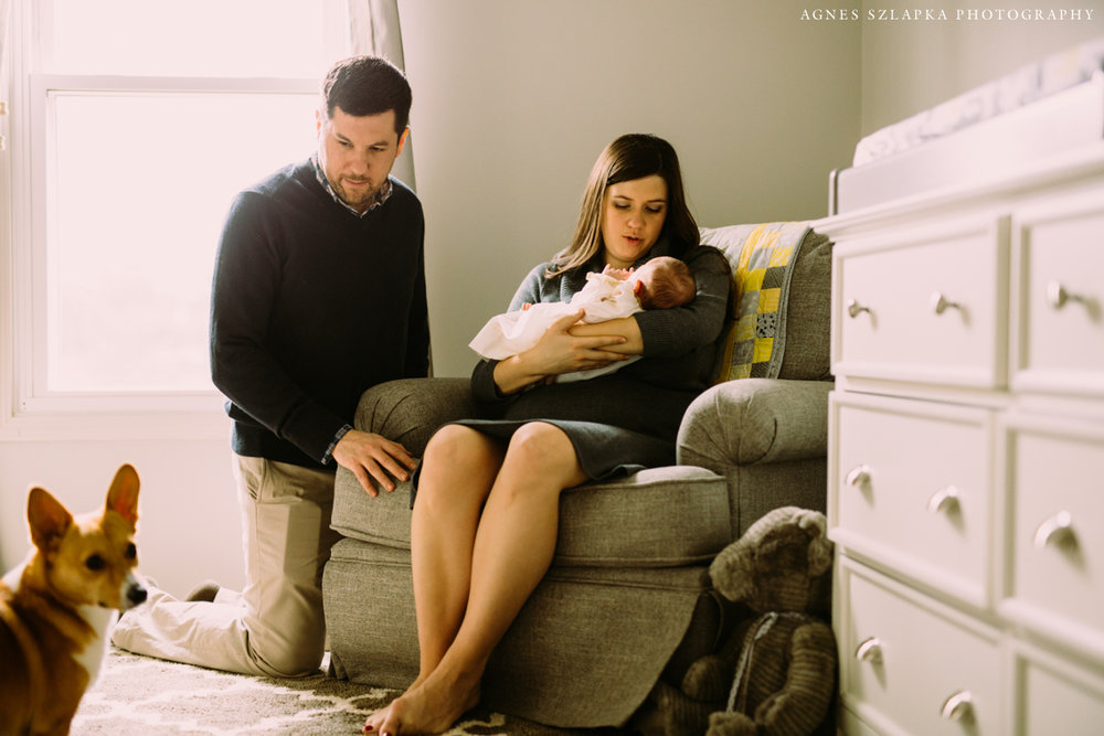 new parents sitting in baby nursery | cleveland, ohio newborn portraits