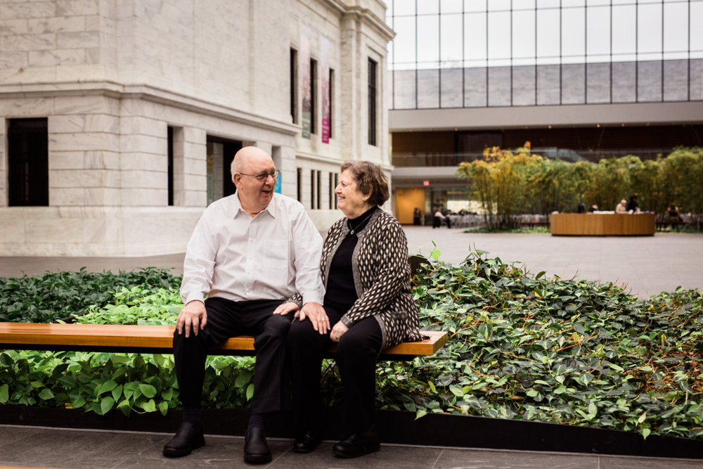 older married couple sitting on bench at museum of art | cleveland, ohio family photographer