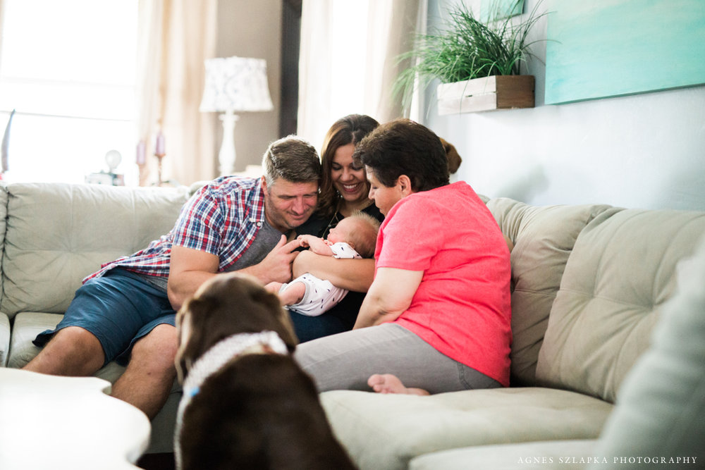 family of three and grandma in living room | cleveland lifestyle newborn photography
