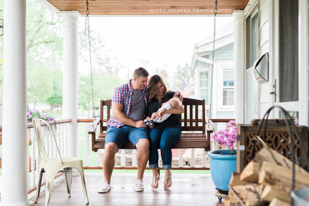 parents with infant baby boy on porch swing | cleveland, ohio lifestyle newborn photography