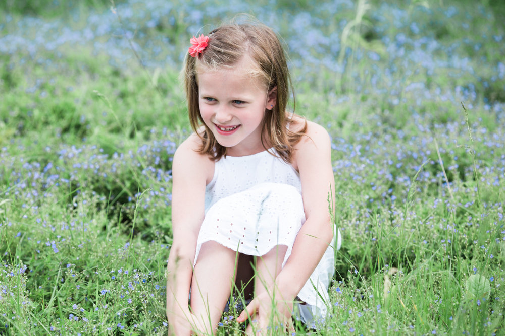 seven year old girl sitting on purple flowers | cleveland, ohio kids photography
